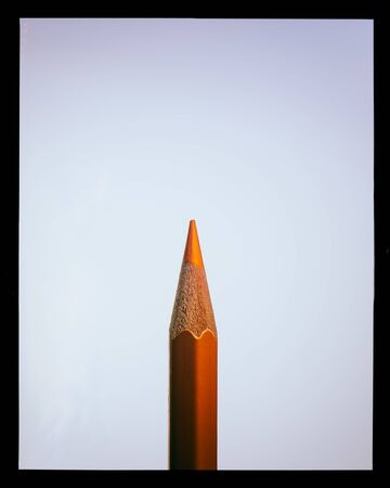 single orange pencil lies on a light background and in a black frame, close-up. Cover for design.