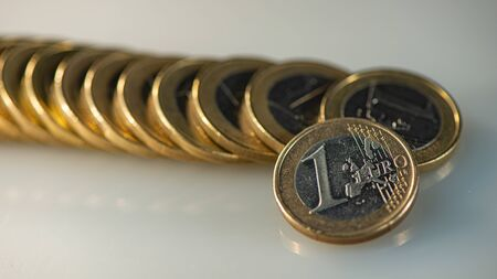 One euro coin on the background of a lying stack of euros. Business concept. Web banner.