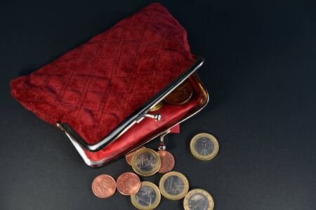 open red wallet and coins of eurocents and euros lie on a black background. Business concept. Фото со стока