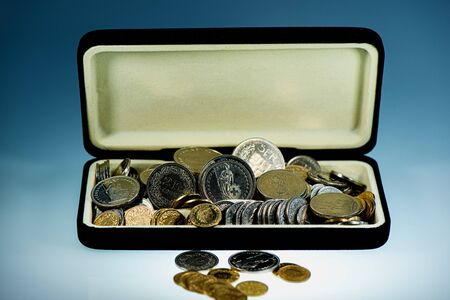 Swiss coins and francs are in an open box against a blue background. Business concept. Web banner. Фото со стока
