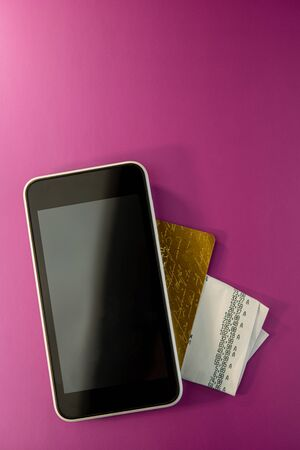 Mobile phone, credit card and sales receipt are on a lilac background. Business concept.