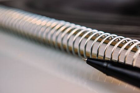 Black pen and metal spiral notepad. Business concept.