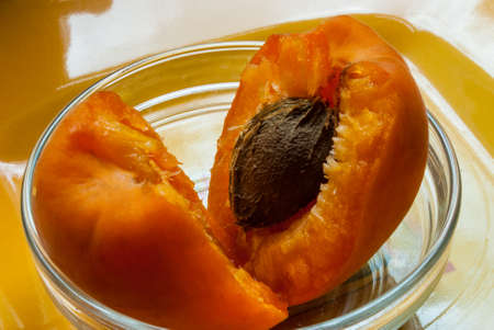 apricot fruit is broken into lobes with a bone lying in a glass saucer. Summer harvest.