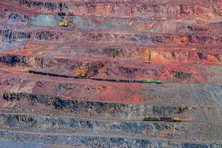 Open pit iron ore mining. Loading of mined ore and delivery by rail and dump trucks. Ukraine. Europe.