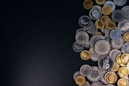 Swiss franc coins lie on a dark background. Business concept.