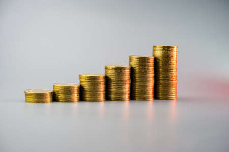 Stacks of golden coins in ascending order on a light gray background. Business concept.