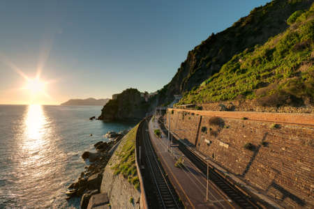 liguria: Railway station near the sea and mountains during the sunset Stock Photo