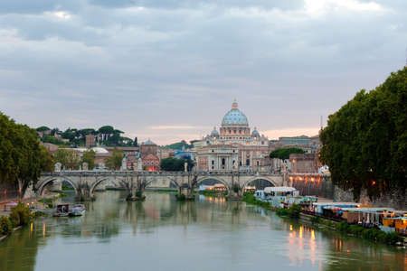 tevere: Evening view at the Angelo bridge and St. Peters Basilica in Rome, Italy Stock Photo