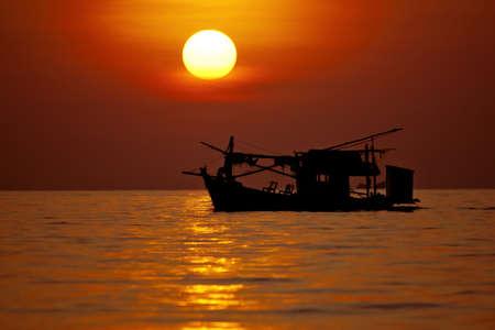 Small ship and big beautiful sun photo