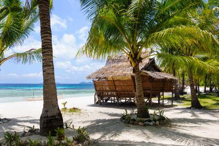 Small hut on the white sand beach near the azur sea photo