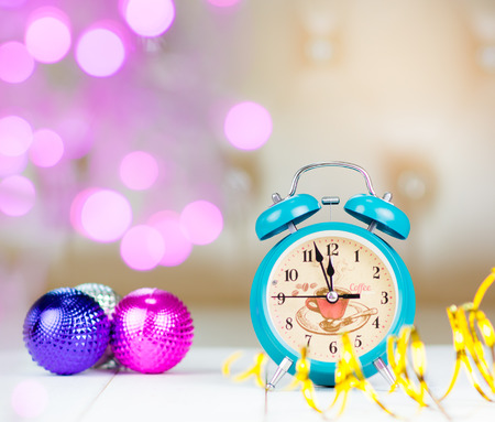 end month: Retro green alarm clock with five minutes to midnight. Decorations christmas balls and ribbons on bokeh Christmas lights background. selected focus. retro style filter Stock Photo
