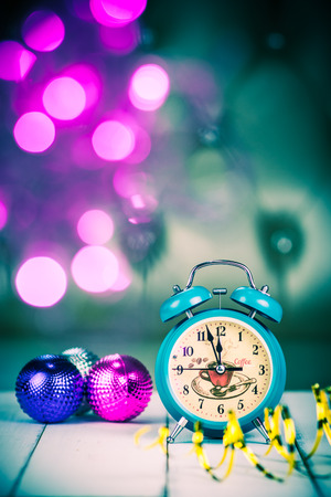 Retro green alarm clock with five minutes to midnight. Decorations christmas balls and ribbons on bokeh Christmas lights background. selected focus. retro style filter Stock Photo