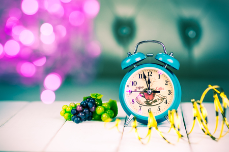 end month: Retro green alarm clock with five minutes to midnight. Decorations grapes and ribbons on bokeh Christmas lights background. selected focus. retro style filter