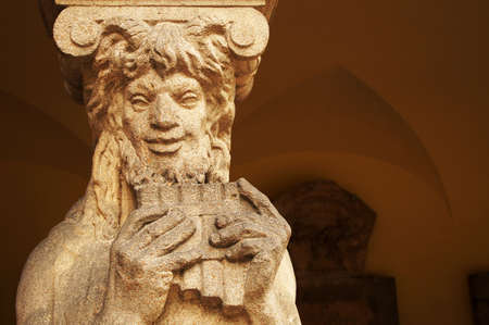 and he shines: Pan the god of shepherds is available here as impressively designed column and over looks the contrary Consider appraisingly. In the strong hands he holds his famous pan flute. The bright sandstone of the column shines brightly against the dark yellow bac Stock Photo