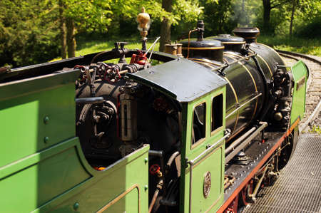 synonym: Side view of a historic narrowgauge railway. It looks out over the Tenter in the cab of the green painted Lock. The black boiler shines in the sun. A synonym for nostalgia Strength and beauty.Seitenansicht on a historic narrowgauge railway. It looks out o