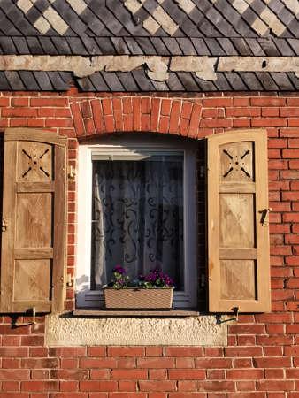 Historisches Backstein Wohnhaus mit alten Holz Fensterläden. Auf dem Fenstersims steht ein Blumenkasten Standard-Bild