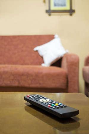 emphasising: Lonely telecomando in salotto tavolo, sottolineando la dipendenza tv  Archivio Fotografico