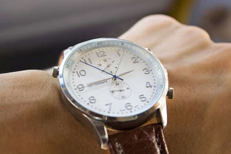 Hands close-up checking the time on a wrist watch