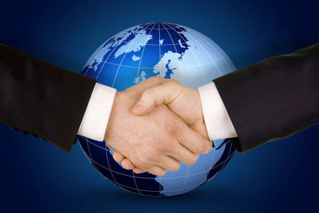shakes hands: Business handshake. Image of businesspeople handshake on the world globe background,