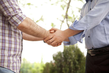 sincere: Natural outside and sincere handshaking. Stock Photo