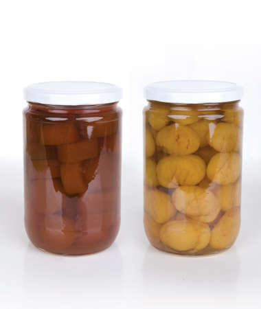 Home canning jars of fall harvest vegetable on white background. Zucchini and chesnut jam.