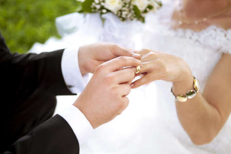 Wedding day. Groom putting a ring on brides finger. Stock Photo