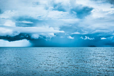 Rain cloud over the sea. .Island be hide the rain between the storm and the sunlight. Filling lonely and blues. Stock Photo