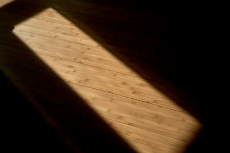 detail of the projection of sunlight when paving through a window and reflecting on a wooden floor