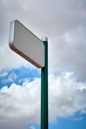 detail of a green pole with indicator signal on a blue and cloudy sky