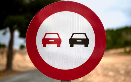 detail of a no overtaking traffic sign with a blue sky and trees in the background