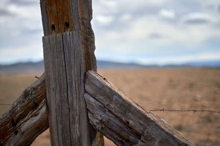 detail of a part of a wooden fence very deteriorated by the weather fencing a farm with wild cattle on an ocher ground and a cloudy and blue sky Imagens