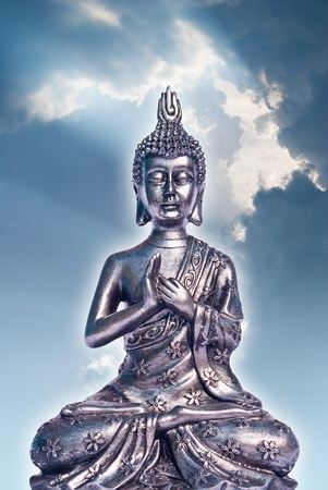Metallic buddha on blue sky background