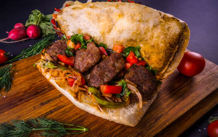 Delicious Turkish Meatballs Sandwich, Kofte Ekmek. Ingredients with bread crumbs, butter, sliced onion, parsley, tomato, pickles and seasoning spices. Hamburger serving on wood table background. Zdjęcie Seryjne