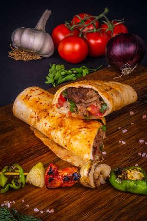 Turkish and Arabic Traditional Ramadan Adana Kebab Roll Wrap serving with yogurt, aubergine salad and hot pepper pickles on rustic wooden background. 免版税图像