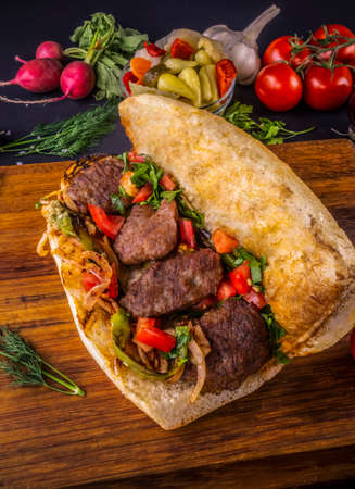 Delicious Turkish Meatballs Sandwich, Kofte Ekmek. Ingredients with bread crumbs, butter, sliced onion, parsley, tomato, pickles and seasoning spices. Hamburger serving on wood table background. 免版税图像