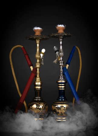 East smoking hookah. Arabian shisha. dark background with smoke Reklamní fotografie