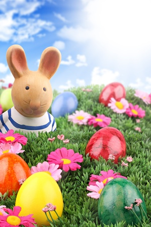 Easter bunny looking at his colorful easter eggs on meadow with blue sky. Stock Photo - 9076738