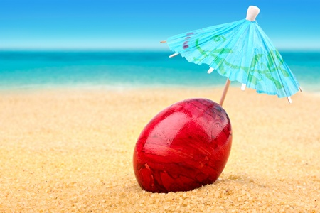 Easter egg with sunshade at the beach Stock Photo