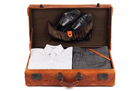 zapatos escolares: Una vieja maleta de cuero con ropa de negocios sobre fondo blanco