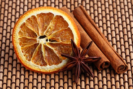orange slice with anis and cinamon sticks on bamboo mat photo