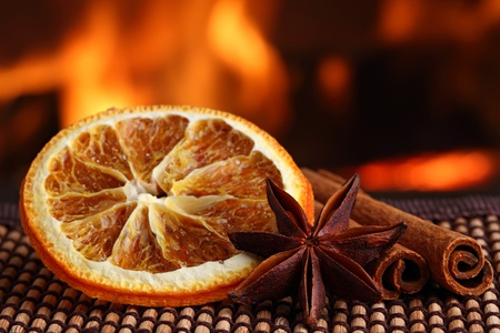 christmas tea: orange slice with anis and cinamon sticks on bamboo mat in front of fireplace