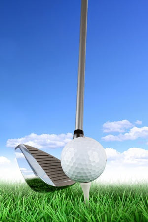 golf equipment: golf club with ball and tee on green in front of blue cloudy sky