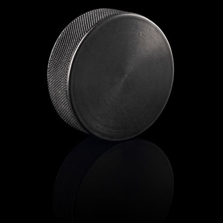lowkey: ice hockey puck in front of black background