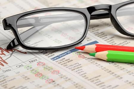 fondos negocios: vasos y lápices verdes rojos en el periódico con gráficos de acciones