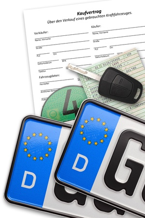 Duitse nummerplaten met contract sleutel en papieren op witte achtergrond