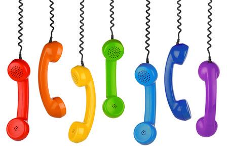 fila de microteléfonos viejos en el fondo blanco Foto de archivo