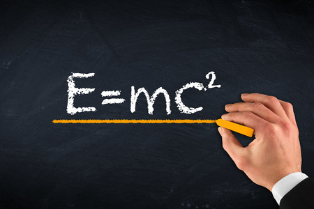 mc2: chalk board with hand and theory of relativity Stock Photo