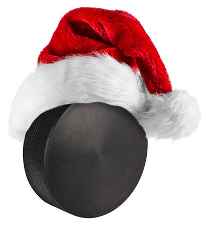 santa hat on ice hockey puck on white background