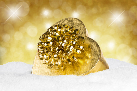golden heart shaped box in snow photo