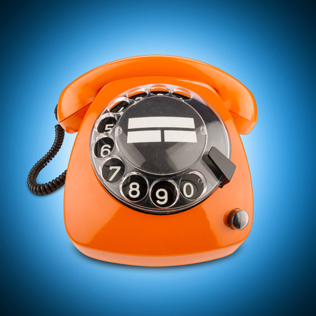 an old orange phone with rotary dial photo